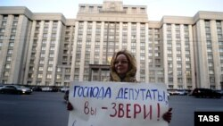 Женщина протестует против принятия нового закона, запрещающего усыновления российских детей американцами. Москва, 19 декабря 2012 года.