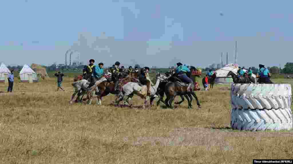 Казахская национальная игра кокпар, встречаются команды Павлодара и Экибастуза. На заднем планы видны дымящиеся трубы предприятий промышленного города Павлодар.
