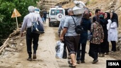 گروهی از مردم در حال خروج مناطق سیلزده در جاده کرج چالوس
