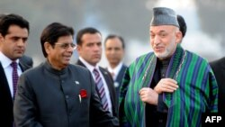Afghan President Hamid Karzai (right) arrives at New Delhi's Palam Airport.