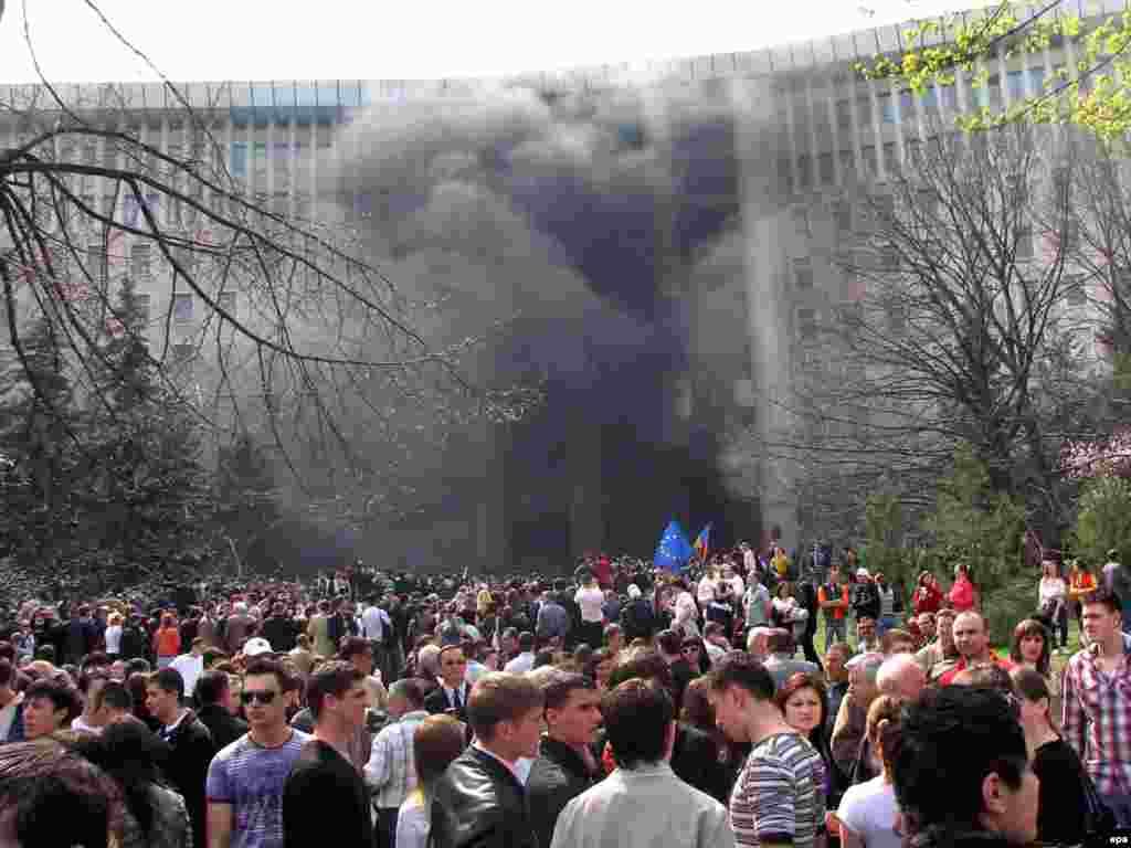 Caption: epa01690564 Young Moldovan protesters wave European Union (EU) flags and shout anti-communist slogans as smoke billows from a fire outside the parliament building in Chisinau, Moldova, 07 April 2009. Thousands of anti-communists protesters, most of them students, gathered to contest parliamentary elections results, asking for new elections. Although Moldova's ruling communist party gained enough votes to hold on to power in parliament on 05 April 2009, they lacked the number of seats to install a new president.