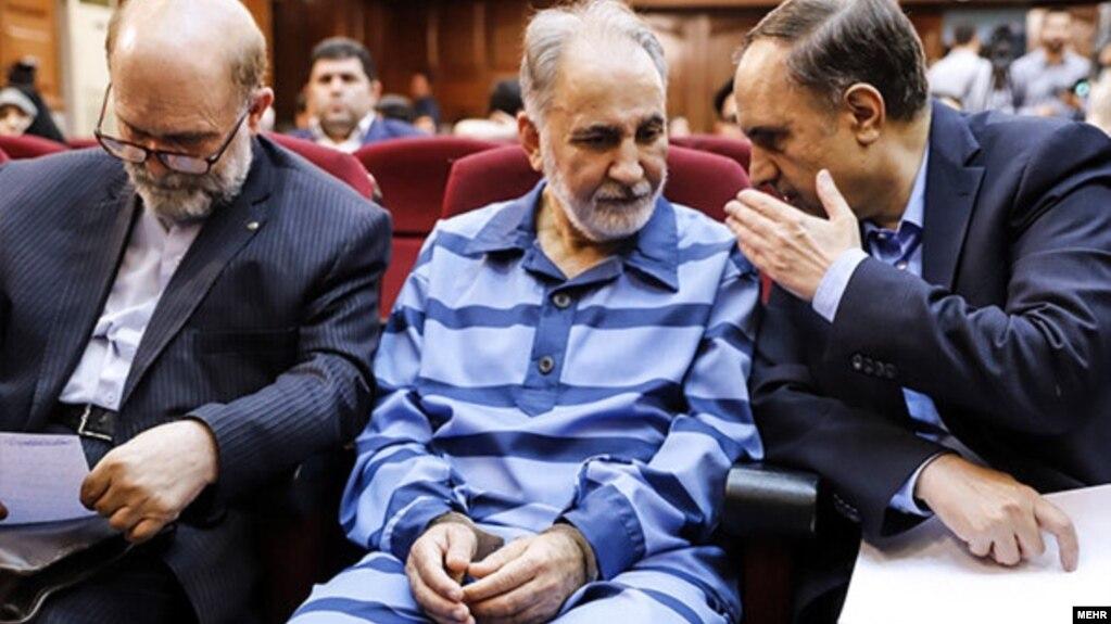 Mohammad Ali Najafi (center) in handcuffs in a Tehran court