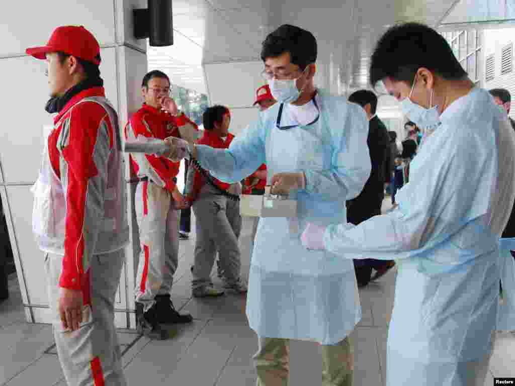 Djelatnici Crvenog križa mjere nivo radijacije u Nagahamau, 14.03.2011. Foto: Reuters / Kyodo
