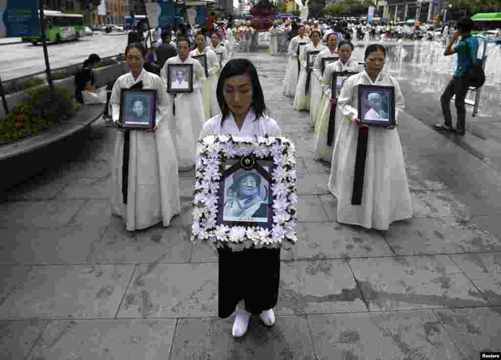 Participants carry the portraits of Korean women who were made sex slaves by the Japanese military during World War II during a requiem ceremony for former comfort woman Lee Yong-nyeo (center portrait) in central Seoul. Lee, who was one of the last surviving comfort women, died on August 11. (Reuters/Kim Hong-Ji)