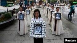 Участники поминальной церемонии несут портреты женщин, превращенных в сексуальных рабынь в японских борделях во время Второй мировой войны, Сеул, 2013 год.
