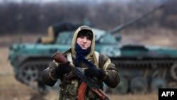 Orsýetçi separatist Ukrainanyň hökümet güýçlerinden awgust aýynda söweşde basyp alnan tankyň öňünde, Ilowaisk, 18-nji noýabr, 2014.