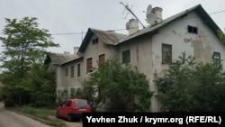 В доме №5 некоторые окна заколочены или разбиты