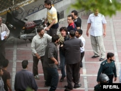 Protester being arrested by plainclothsmen during disturbances following the controversial election in June 2009.