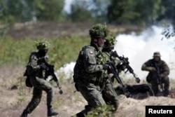 Учения войск НАТО на базе в Адажи (Латвия). Многие латыши воспринимают это как гарантию безопасности