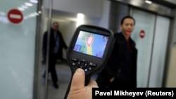 Алматы әуежайында СЭС қызметкері Қытайдан келген жолаушылардың дене қызуын тексеріп тұр. 21 қаңтар 2020 жыл.