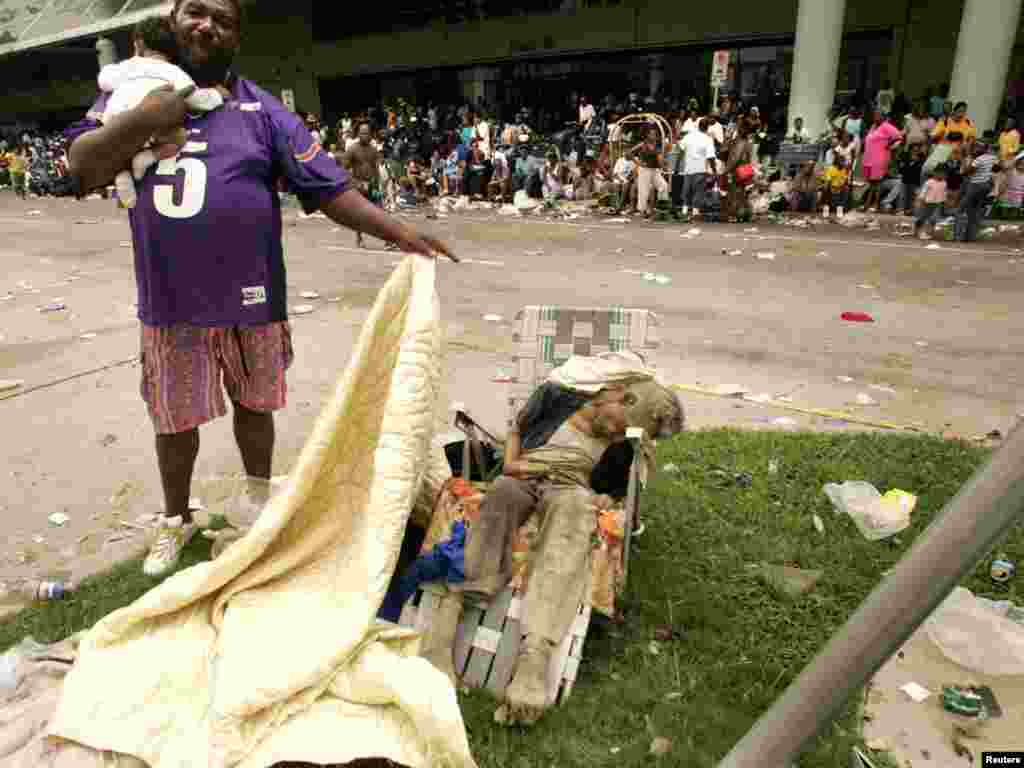 A man holding a baby uncovers the body of a dead man, suspected to have been sitting there for two days, outside the New Orleans Convention Center September 1, 2005. Several people among the thousands of stranded hurricane evacuees have died while waiting outside the building, with no sign of imminent help on the way. REUTERS/Rick Wilking