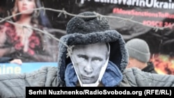 A protester holds up a mask of Russian President Vladimir Putin during a rally against Russian aggression in Kyіv. Freedom House says Moscow further reduced the space for public dissent and political opposition at home in 2016.
