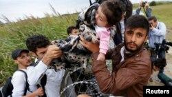 پناهجویان سوری در حال گذر از روی حصار مرز مجارستان و صربستان