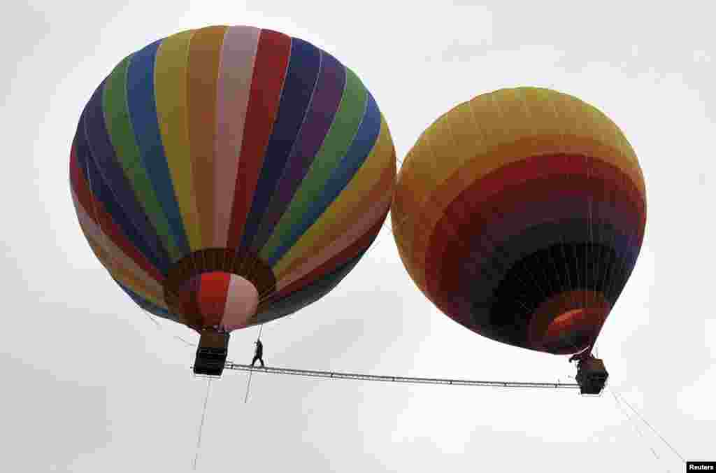 Aisikaier Wubulikasimu, a 40-year-old Uyghur acrobat, walks on an 18-meter-long tightrope strung between two hot air balloons in Shilin county, in China's Yunnan Province. (Reuters/Stringer)