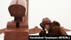 Алтынбек Сәрсенбайұлының жары Салтанат Атушева жұбайының зираты басында. Алматы, 11 ақпан 2012 ж.