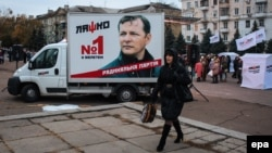 A woman passes a small truck with a preelection billboard with a portrait of Oleh Lyashko, the leader of Ukraine's populist Radical Party, in the eastern town of Kramatorsk, near Slovyansk, on October 23.