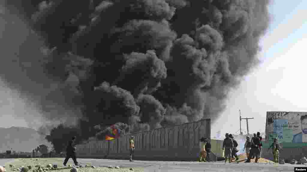 Smoke billows from a fuel tank supplying NATO troops after it was set on fire by protesters during a demonstration in Jalalabad on February 22.