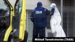 Сотрудник скорой надевает защитный костюм, Москва