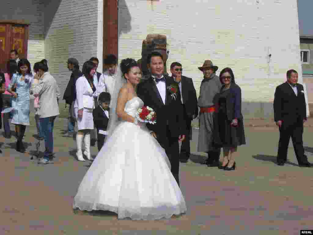 Newlyweds pose outside the monastery. - Mongolians often plan their personal lives around auspicious dates on the Buddhist calendar, and brides and grooms often include a monastery in the sites they visit for photographs after the wedding ceremony.