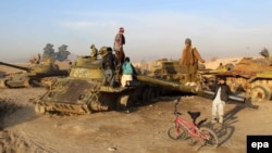 Children in Afghanistan play in a junkyard of Soviet-era tanks left over from Moscow's disastrous occupation of the country between 1979 and 1989.