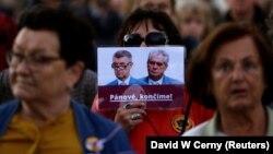 Демонстрантка носи постер со кој бара оставка од лидерот на АНО Андреј Бабиш и претседателот на Чешка Милош Земан на протест пред Прашкиот замок на 17 октомври 2017