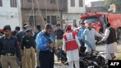 Police officials examine the site of a suicide bomb blast in Peshawar on November 9.