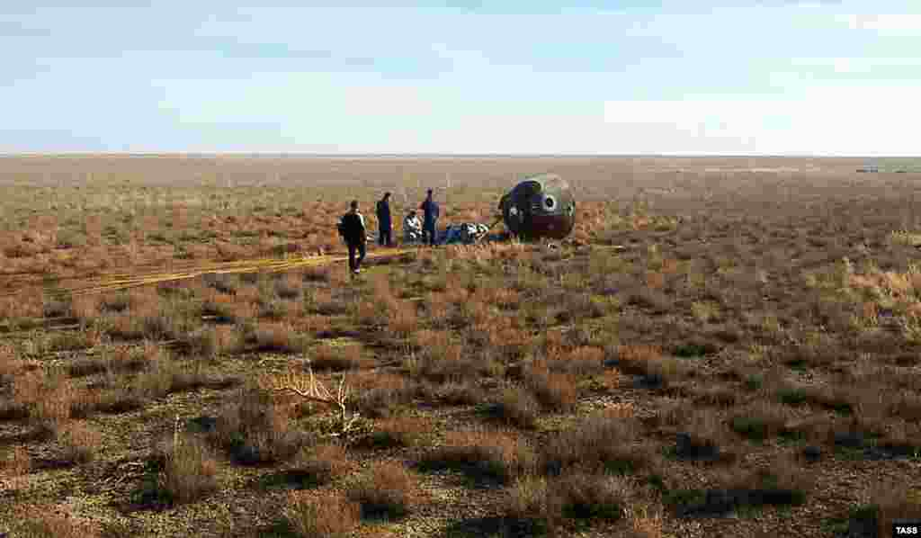 "A search-and-rescue team works at the landing site on the desolate Kazakh steppes of the Soyuz MS-10 space capsule after a launch to the International Space Station (ISS) was aborted due to a problem with a booster rocket. The crew of two landed safely after what is called a ""ballistic descent."" (TASS)"
