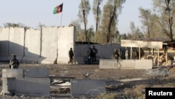 Afghan security forces stand guard at the entrance gate of Kandahar Airport on December 9.