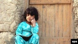 An Afghan girl sits outside her house in Kabul (file photo)