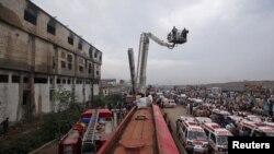 Өртенген фабриканың сыртында тұрған құтқарушылар мен жедел жәрдем көліктері. Карачи, Пәкістан, 12 қыркүйек 2012 жыл.