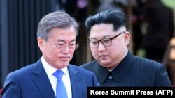 North Korea's leader Kim Jong Un (L) and South Korea's President Moon Jae-in (R) walk to announce a joint statement after a signing ceremony near the end of their historic summit at the truce village of Panmunjom on April 27, 2018.
