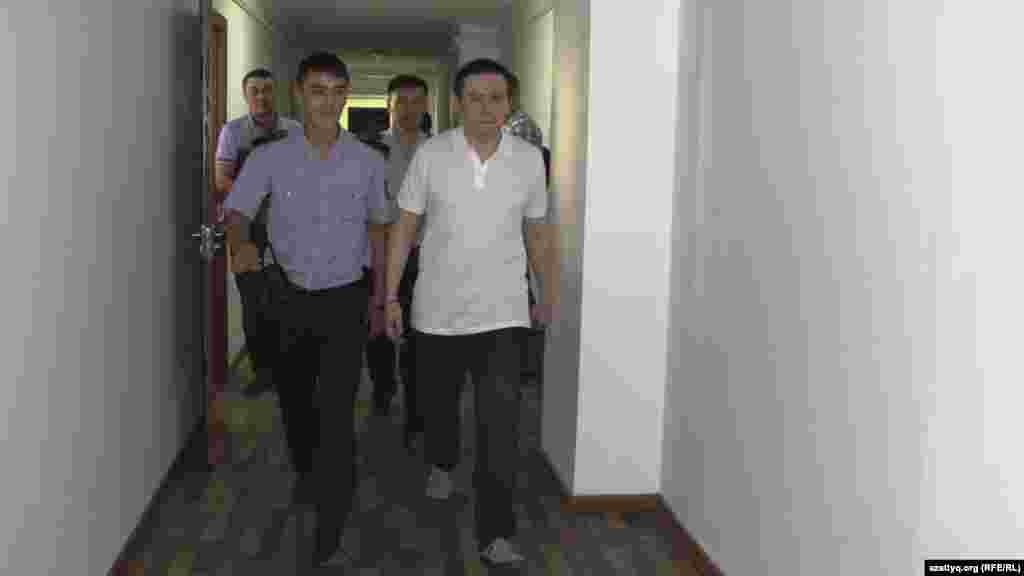 Полиция өкілі қамаудағы журналист Жанболат Мамайды (оң жақта) үкім шығар алдында сот залына әкеле жатыр. Алматы, 7 қыркүйек 2017 жыл.