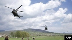 French KFOR watch helicopters take off near Mitrovica, Kosovo.