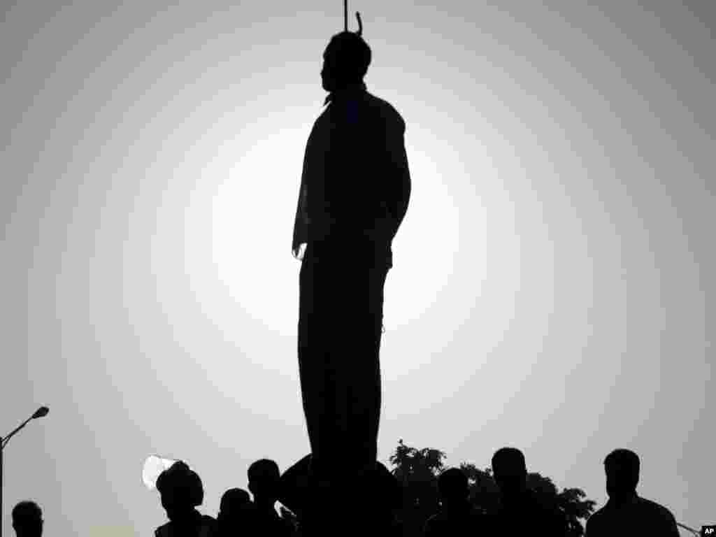 Silhouette of a convicted man, Mahdi Faraji, is seen while he is being hanged in the city of Qazvin, 130 kilometers west of the Iranian capital, Tehran, on May 26. Iran's official news agency reported that five prisoners were hanged in public, including a convicted serial killer. The others had been found guilty of rape and armed robbery. This brought the number of executions to 130 since the beginning of the year. Photo by Hamideh Shafieeha for AP/Mehr