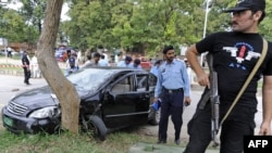 Police inspect the bullet-riddled car of Religious Affairs Minister Hamid Said Kazmi in Islamabad.