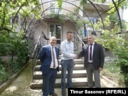 Poluboyarenko (left), Martens (center), and Abazov stand in front of the house that Poluboyarenko offered to the Martenses.