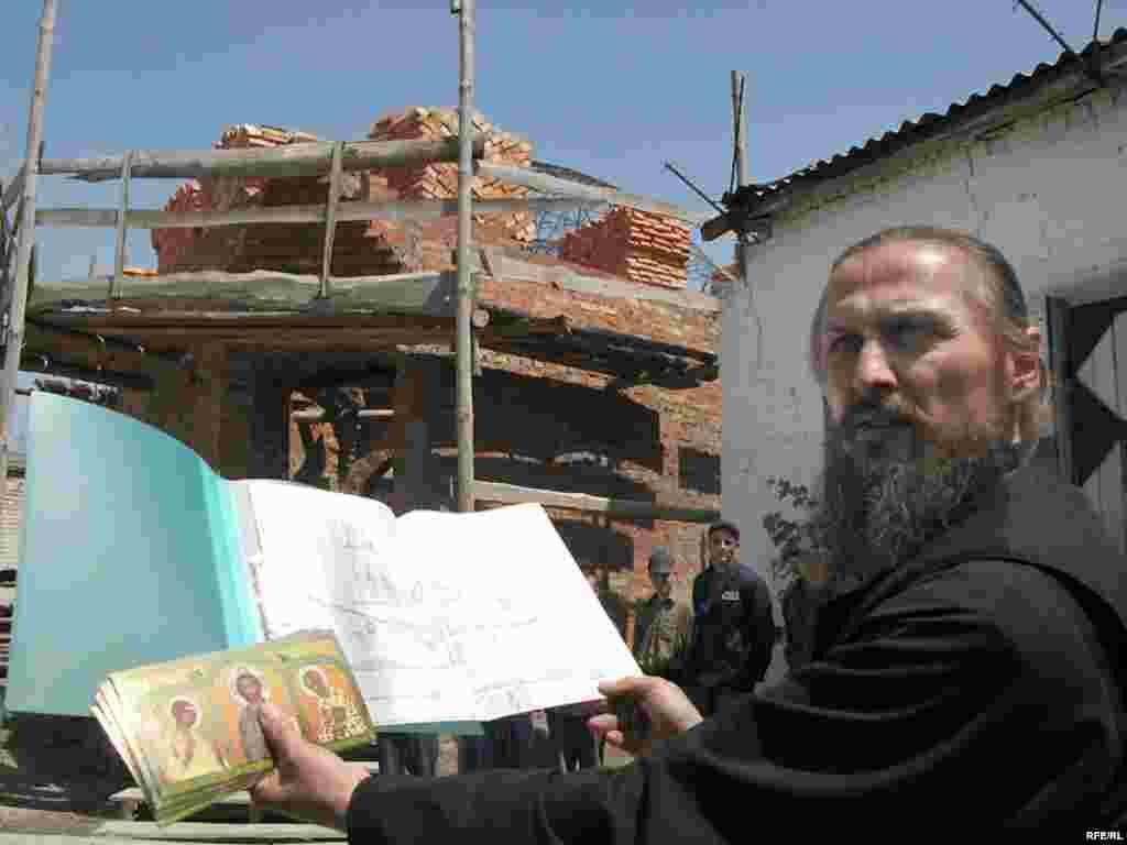 Отець Олег показує проект майбутньої церкви на території колонії. Сам храм буде подібний до корабля, що за словами священника символізує спасіння.