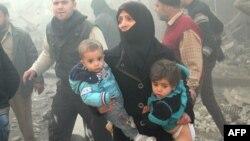 Әуе шабуылы кезінде балаларын көтеріп алған сириялық әйел, Алеппо провинциясы. (Көрнекі сурет)