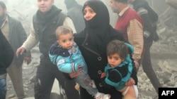 زن سوری فرزندان خود را از محل انفجار در حلب دور میکند
