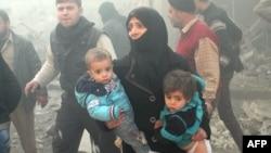 Сирийка с детьми во время воздушного удара по Алеппо. Сирия, 15 декабря 2013 года.