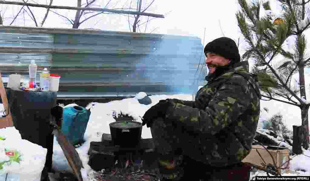 Военный на блок-посту греется у костра. Он с радостью встречает волонтеров из Волновахи.