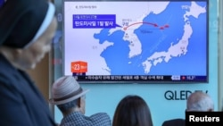 South Korea, Seoul, People watch a news report on North Korea firing a ballistic missile.