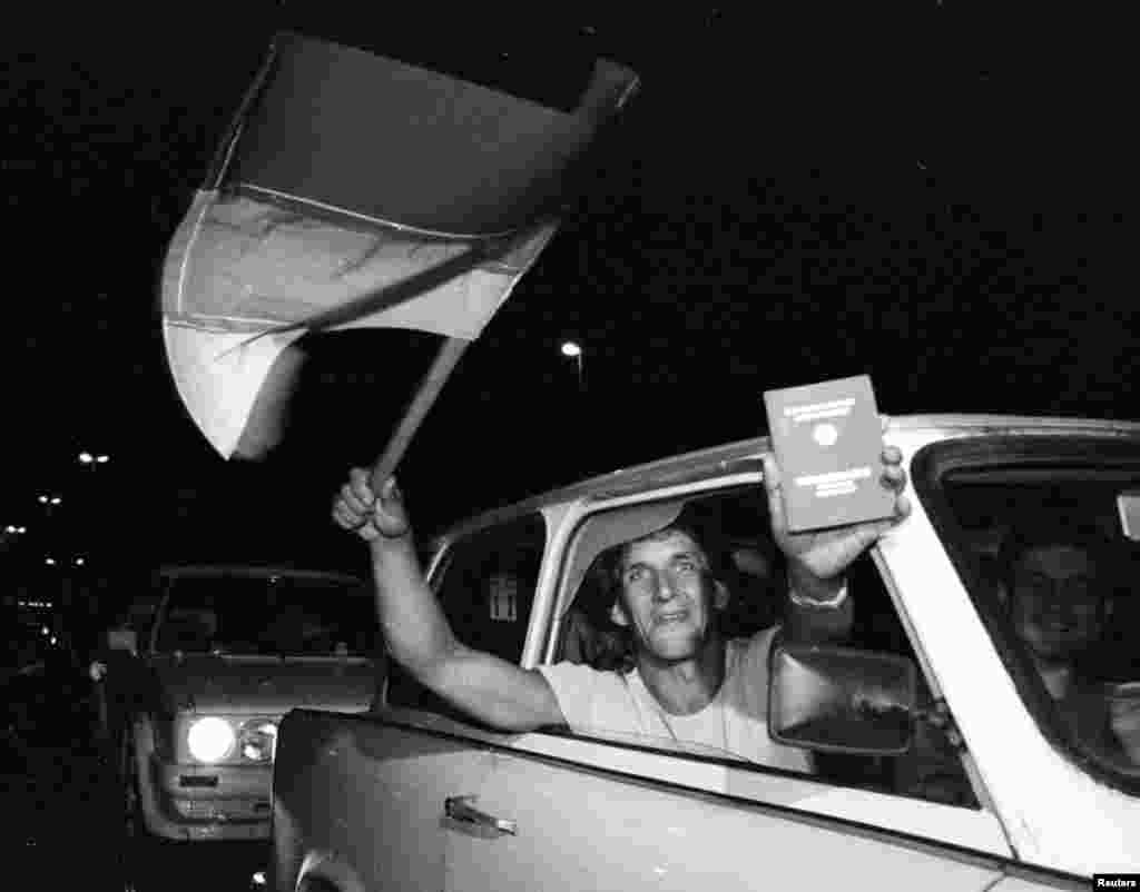 An East German shows off a newly acquired West German passport just before crossing into Austria overnight on September 10-11.