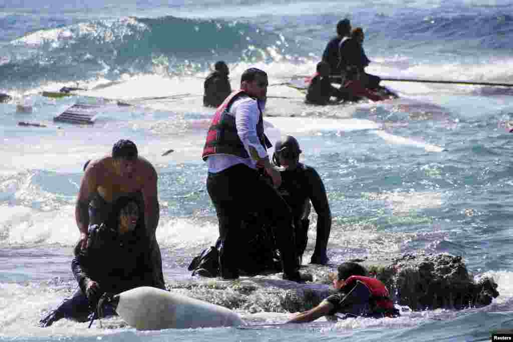 Migrants trying to reach Greece are rescued by members of the Greek Coast Guard and local residents near the coast of the southeastern island of Rhodes. A wooden sailboat carrying dozens of immigrants ran aground April 20 off Rhodes. At least three people drowned. As many as 900 people may have died in a migrant boat disaster off the coast of Libya on April 19. (Reuters/Argiris Mantikos/Eurokinissi)