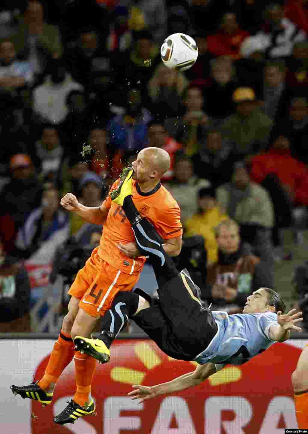 1-е место / Спорт / одиночные фотографии Майк Хатчинс, Южная Африка, Reuters Деми де Зеу из Голландии получил случайный удар ногой в лицо от Мартина Касереса из Уругвая, во время полуфинального футбольного матча на Кубок мира, Кейптаун, 6 июля 2010.