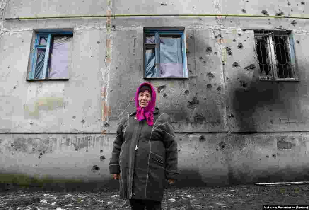 70-летняя местная жительница Лариса Белецкая стоит перед многоквартирным домом, поврежденным во время боев между вооруженными силами Украины и боевиками поддерживаемых Россией группировок, в поселке Голубовское Луганской области, 19 февраля 2020 года