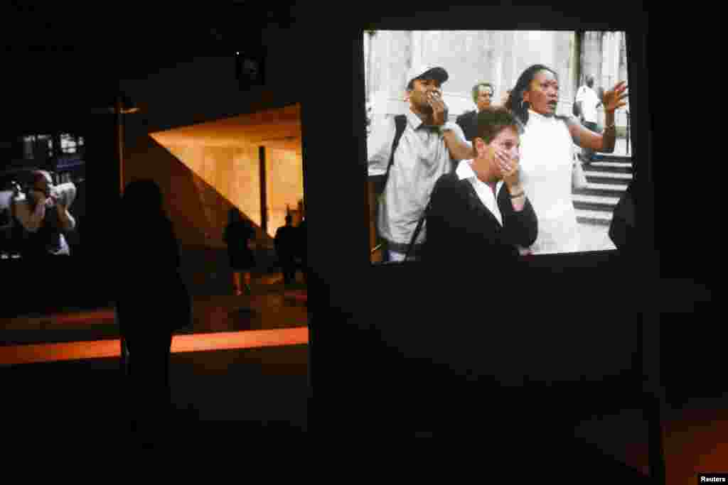 Visitors walk by projections of videos from September 11, 2001.