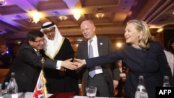 """Hillari Klinton përshëndetet me ministrin e jashtëm turk, Ahmet Davutoglu, në takimin """"Miqtë e Sirisë"""" në Tunizi"""