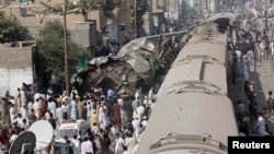 Spectators watch as rescue workers search a train that crashed in Karachi on November 3.