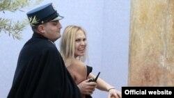 Ватиканда полиция шіркеу билігіне қарсы акция өткізген FEMEN белсендісін ұстап әкетіп барады. Ватикан, 25 желтоқсан 2014 жыл.